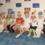 Дети с шапочками в виде небесных тел сидят на стульчиках