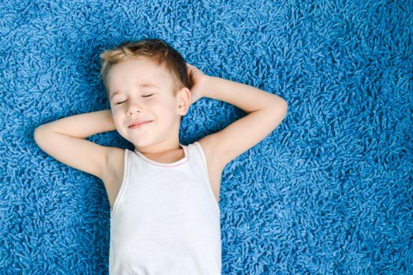 Мальчик с зыкрытыми глазами лежит на ковре