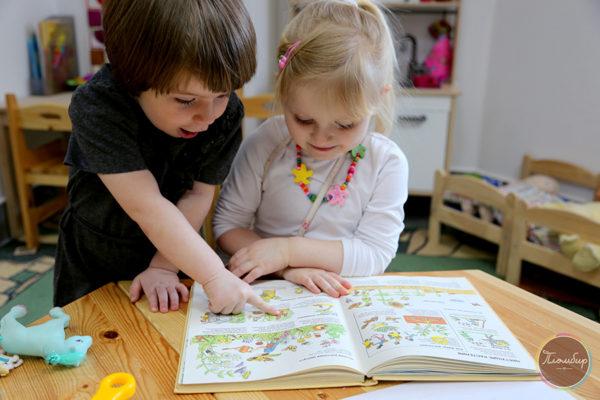 Мальчик и девочка рассматривают иллюстрации в книге