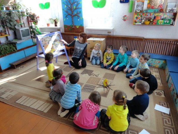 Дети и педагог сидят в кругу и рассматривают иллюстрации на доске