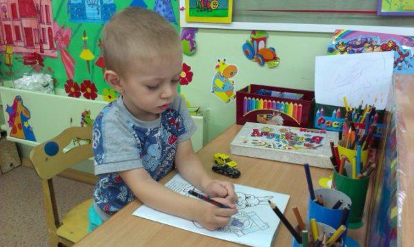 Ребёнок раскрашивает картинку в уголке ИЗО