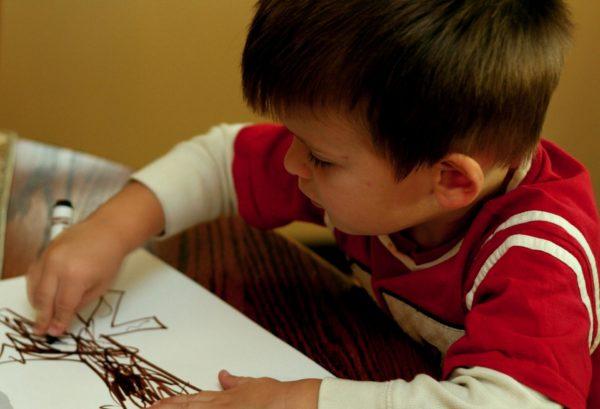 Мальчик рисует фломастером