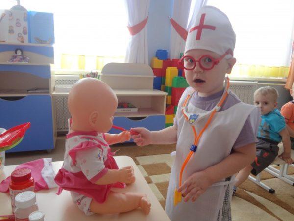 Ребёнок в роли врача играет с куклой