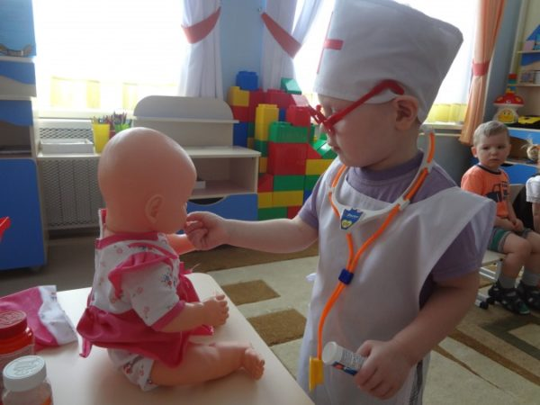 Ребёнок в роли врача лечит куклу