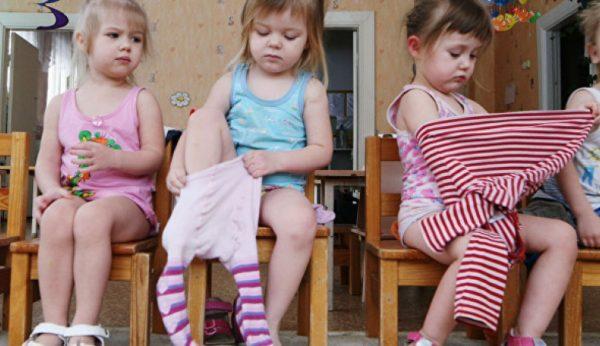 Три девочки одеваются, сидя на стульях