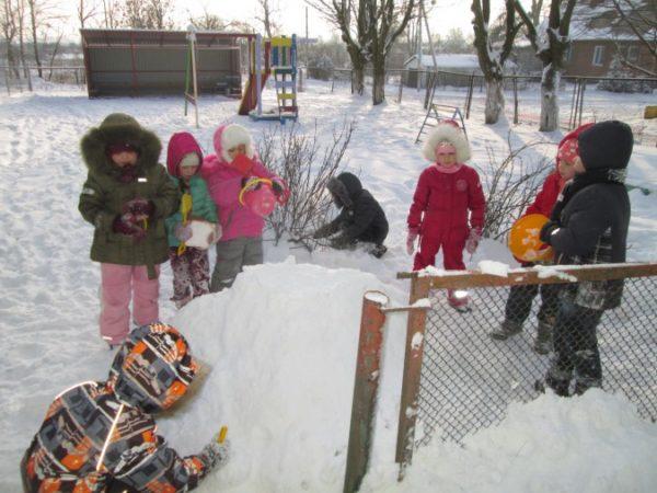 Дошкольники играют со снегом на прогулке
