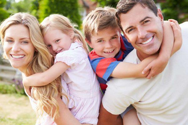 Мама, папа и двое детей, все улыбаются