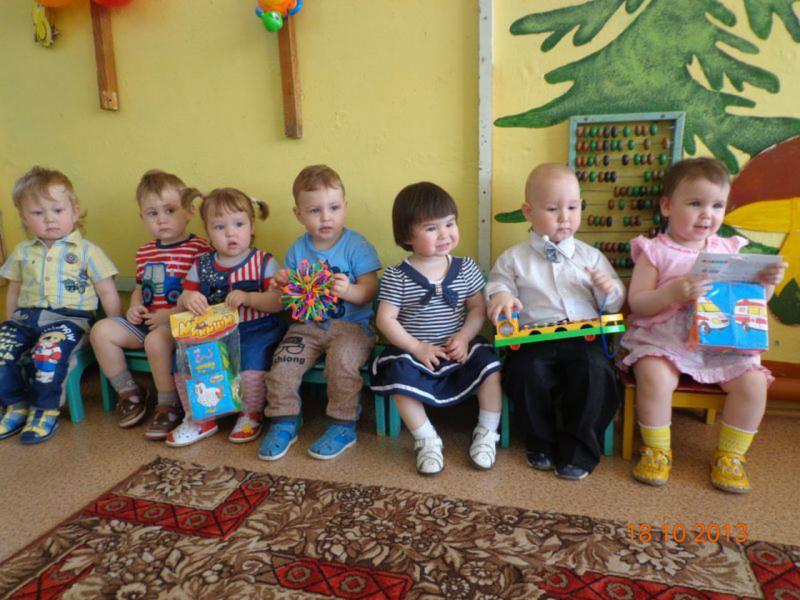 Семеро детей сидят на скамейке, у двух девочек в руках кубики-мякиши, у мальчика мозаика-фонарик