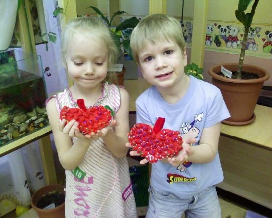 Мальчик и девочка держат в руках поделки — красные сердечки