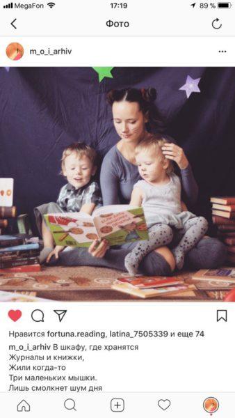 Мама читает двум малышам, сидящим у неё на коленях