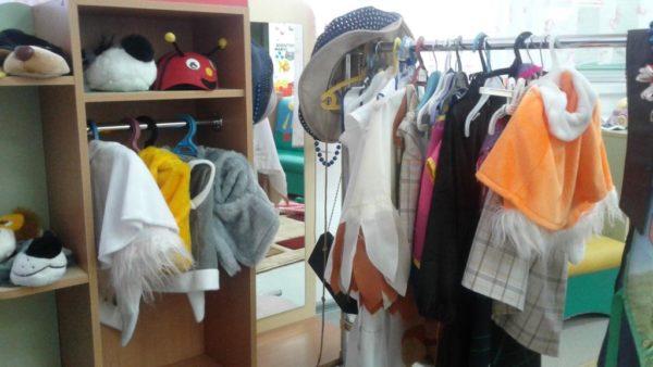 Справа стеллаж с закрытой полкой под шапку-мордочку собачки и божьей коровки, справа — вешалка с костюмами