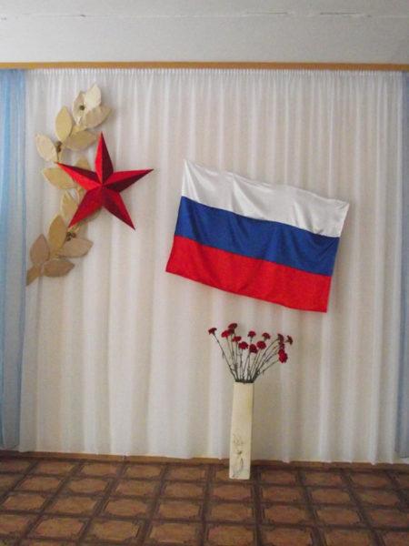 Стена украшена флагом России, звездой и вазой с букетом гвоздик