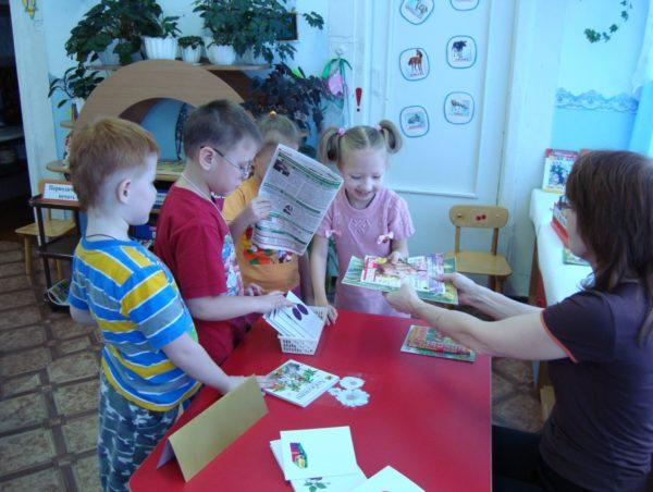 Дети и педагог играют в библиотеку