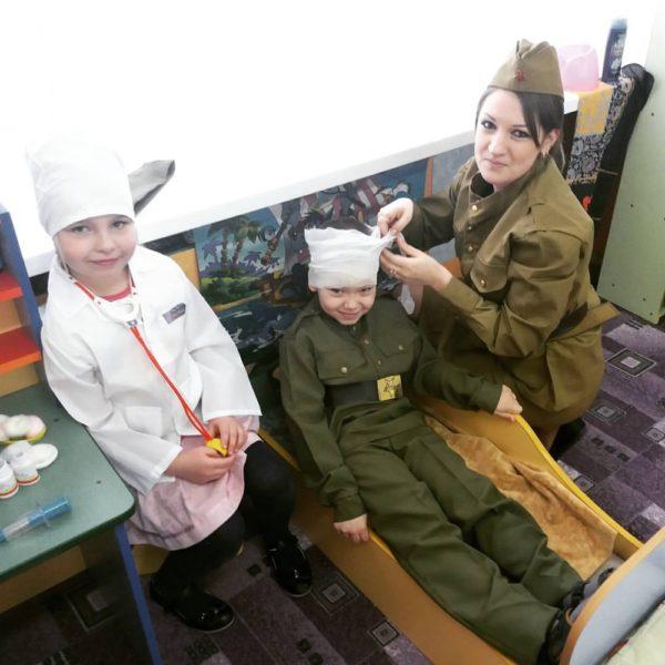 Педагог и двое детей играют в военный госпиталь