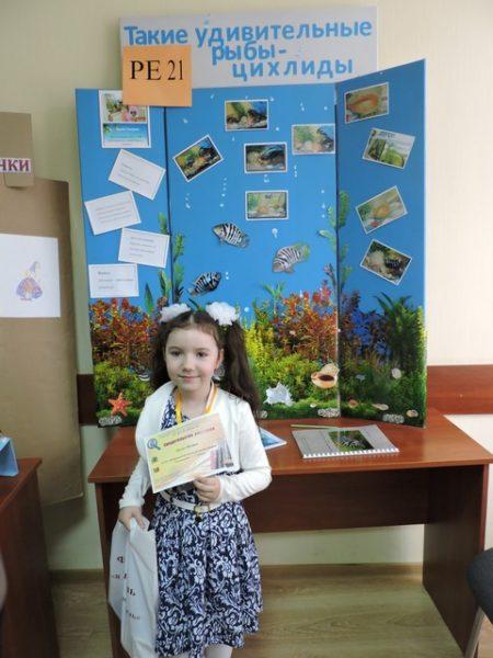 Девочка с грамотой в руках стоит на фоне стенда с фотографиями редких рыб
