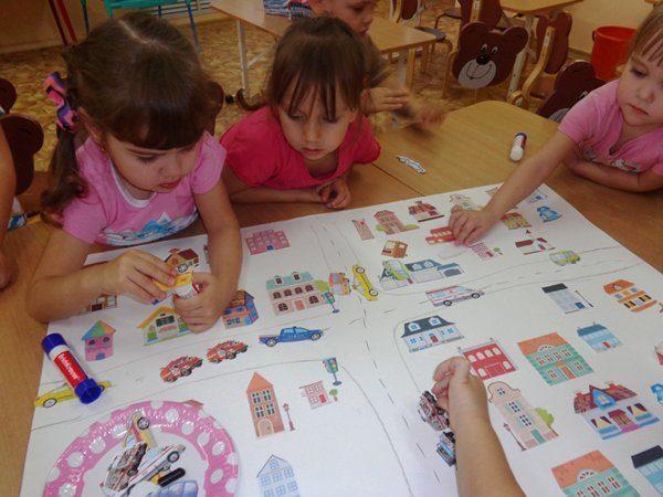 Три девочки наклеивают домики и машинки на ватман