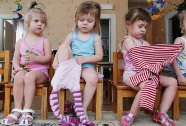 Три девочки сидят на стульях, две из них одеваются