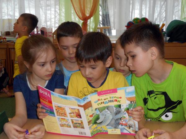 Три мальчика и девочка читают книжку Шёл по улице пиджак