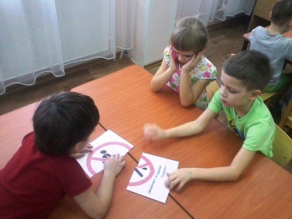 Три мальчика за столом собирают запрещающий знак из двух половинок