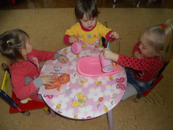 Трое детей купают куклу, сидя за круглым столиком