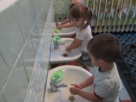Трое детей моют руки