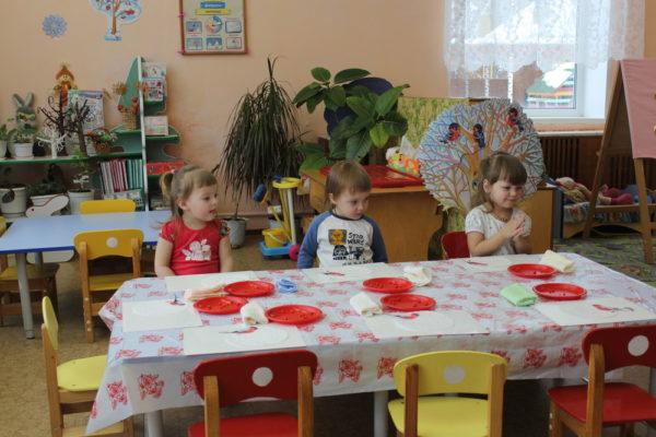 Трое детей сидят за столиками с красными тарелками