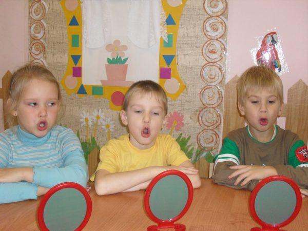 Трое детей выполняют артикуляционное упражнение, перед ними на столе стоят небольшие зеркала