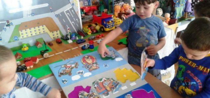 Трое мальчиков вкладывают картинки-пазлы в книгу