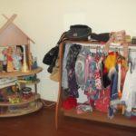 Уголок ряжения: слева куклы на круглых деревянных полках с фанерной крышей, справа — стеллаж с перекладиной под вешалку для костюмов и покой сверху для шляп