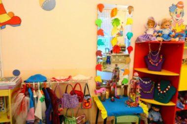 Уголок ряжения: слева стойка с костюмами, справа - красный шкаф с бусами на жёлтых полочках