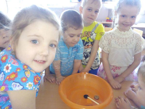 Улыбающиеся дети стоят рядом с тазиком с водой, в котором плавают небольшие предметы