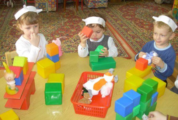 Трое детей играют с большими разноцветными кубиками