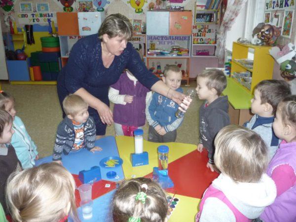 Дети и педагог проверяют, имеет ли вода запах