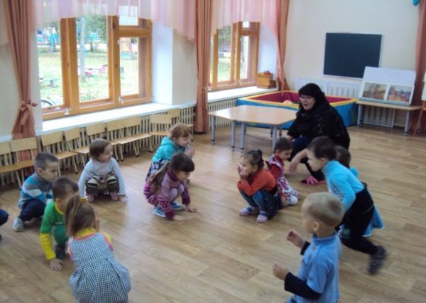 Воспитатель и дети на корточках, педагог что-то объясняет
