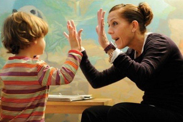 Воспитатель играет в ладушки с ребёнком
