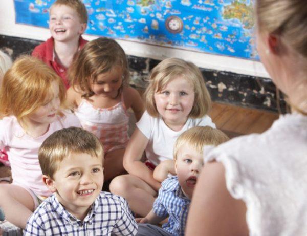 Улыбающиеся дети смотрят на педагога