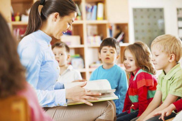 Воспитательница читает книгу детям вслух