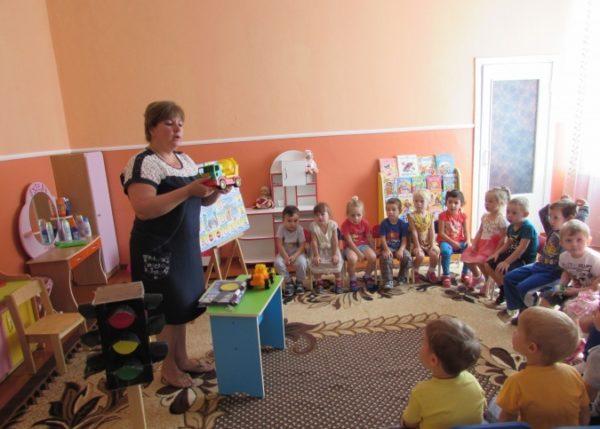 Воспитательница держит машинку и что-то рассказывает детям, сидящим полукругом