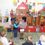 Воспитательница держит в руках фотографию, девочка её описывает, остальные дети сидят на стульях