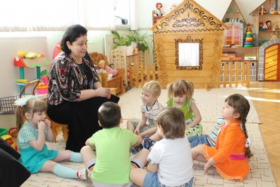 Воспитательница и шестеро детей сидят вокруг неё