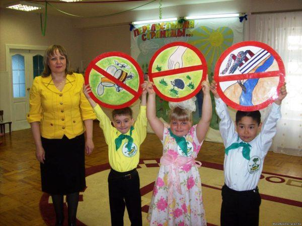 Воспитательница и трое детей, держащих знаки о поведении на природе
