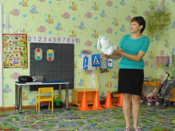 Воспитательница показывает белого зайца, на доске картинки с двумя светофорами