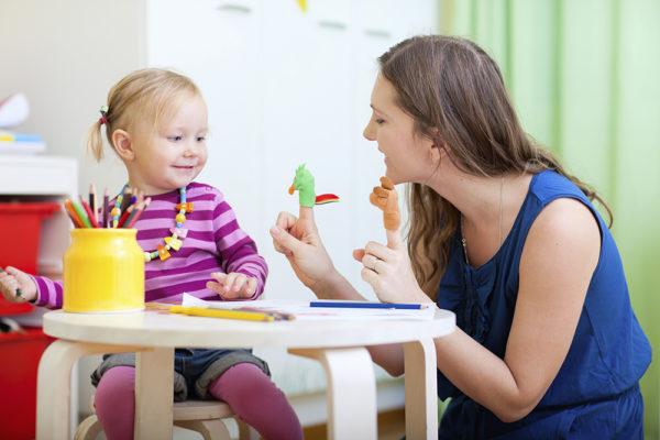 Воспитательница показывает две пальчиковые куклы девочке, сидящей за столом