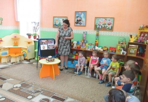 Воспитательница показывает картинки с пасхальными яйцами