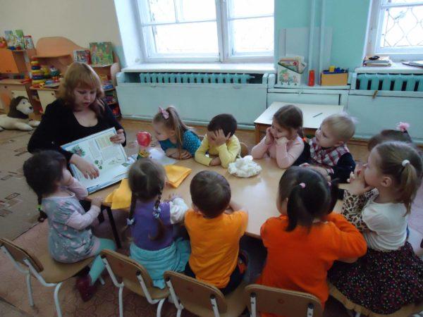 Воспитательница показывает картинку в книге, дети сидят за столом