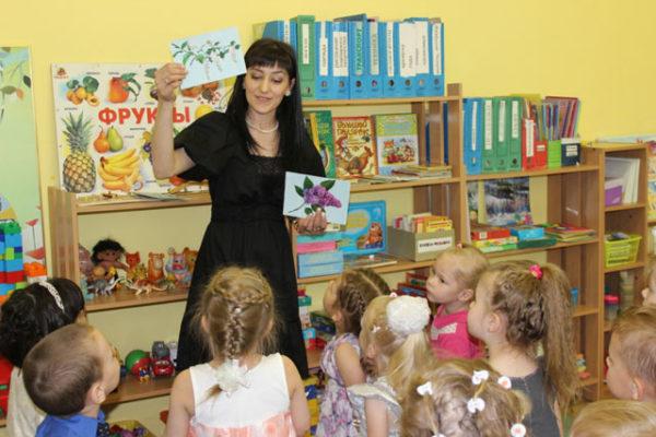 Воспитательница показывает сидящим на стульях детям картинки с цветущей сиренью и акацией