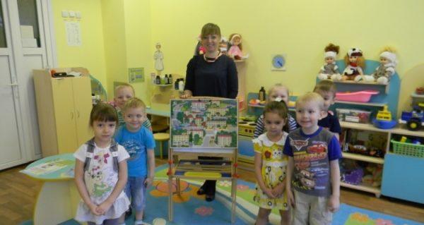 Воспитательница придерживает мольберт с картинкой города, дети стоят по обе стороны от неё