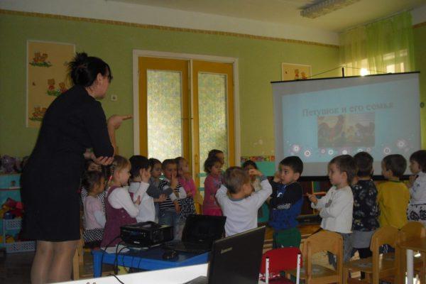 Воспитательница рукой показывает детям петушка, на заднем фоне презентация с изображением петушка и его семьи