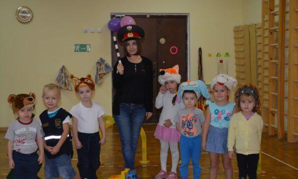 Воспитательница с жезлом и фуражке работника ДПС стоит с детьми в масках животных