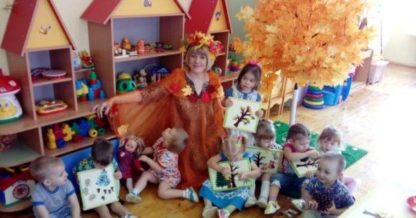 Воспитательница в образе осени сидит с детьми на полу